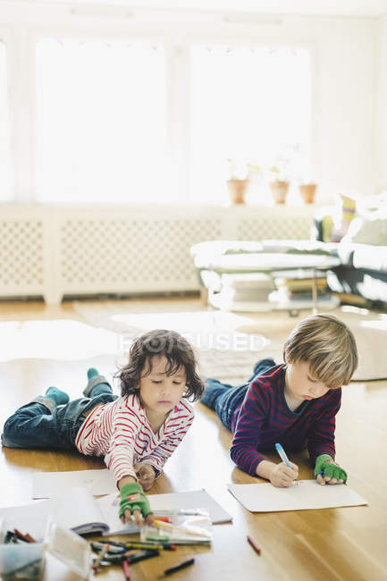 Friends coloring in books while lying on floor at home — Stock Photo