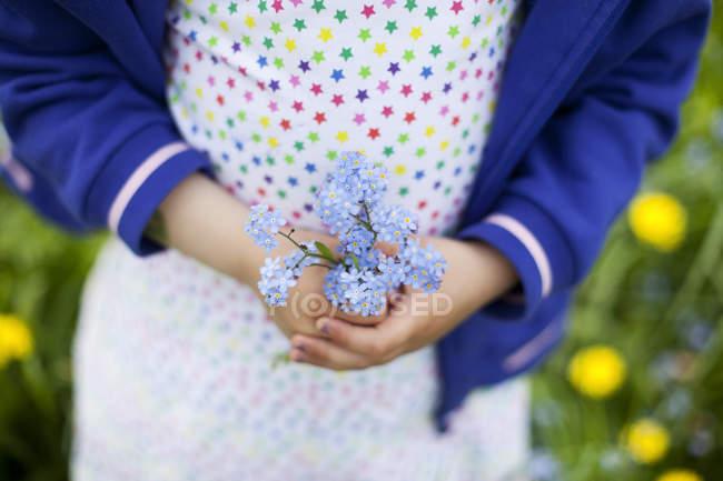 Ragazza che tiene mazzo di fiori blu in mano — Foto stock