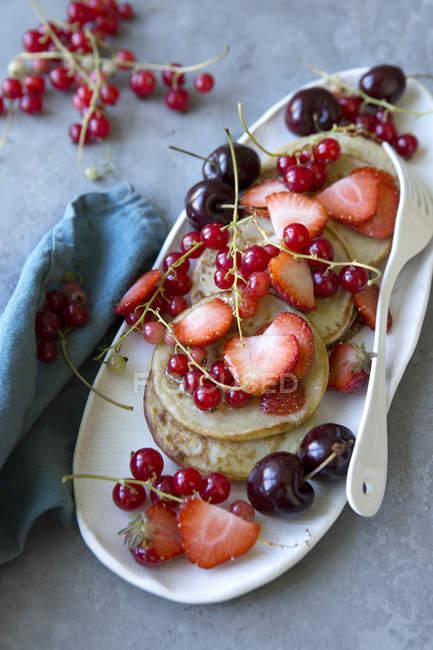 Высокий угол обзора блины и ягод в пластине на столе — стоковое фото