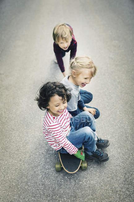 Aus der Vogelperspektive: Kinder genießen das Sitzen auf dem Skateboard — Stockfoto