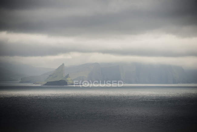 Scenic view of calm sea and mountains under overcast sky — Stock Photo