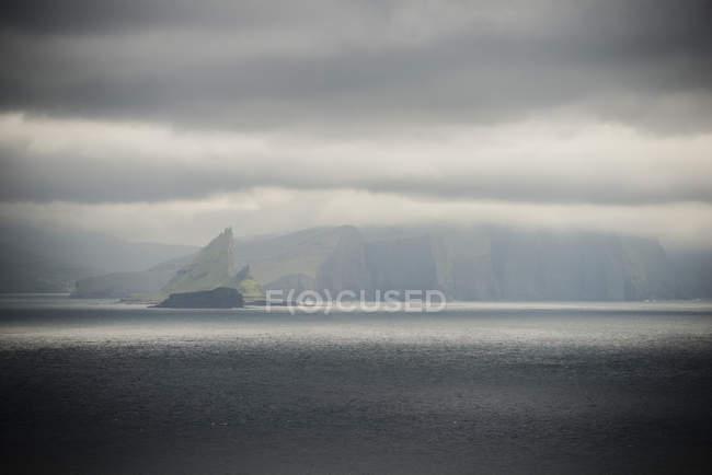 Живописный вид на спокойное море и горы под пасмурно небо — стоковое фото