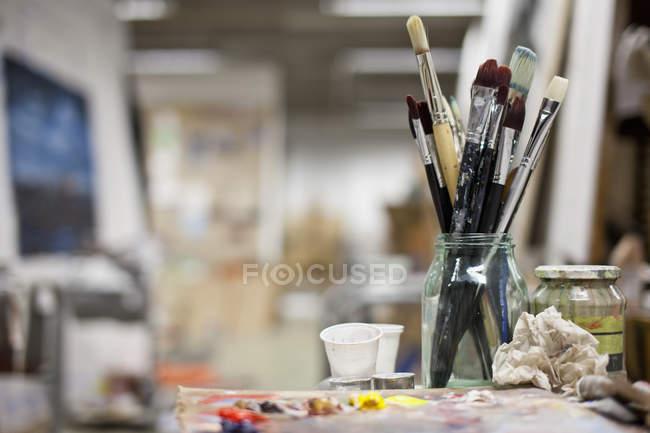 Pinceles sucios en tarro de cristal y paleta con pinturas de aceite - foto de stock