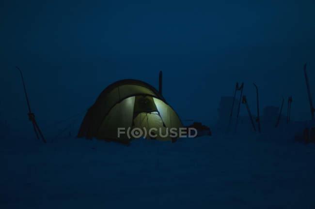 Luz na tenda contra o céu claro da noite — Fotografia de Stock