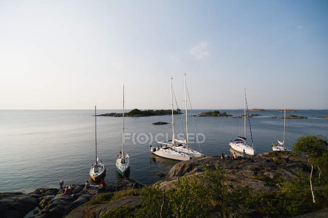 View of white yachts moored near rocky shore and islands in background — Stock Photo
