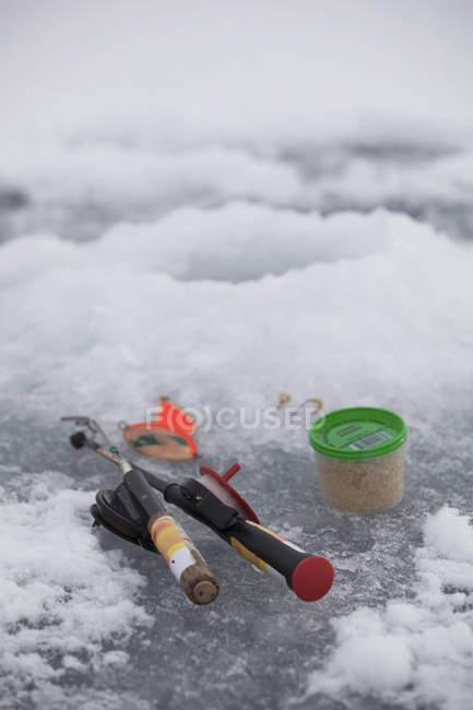 Pesca alimentos y peces en el lago congelado - foto de stock