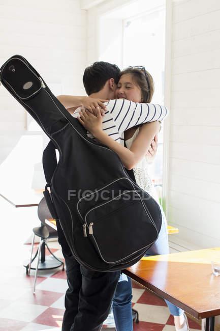 Young man with guitar embracing his girlfriend at restaurant — Fotografia de Stock