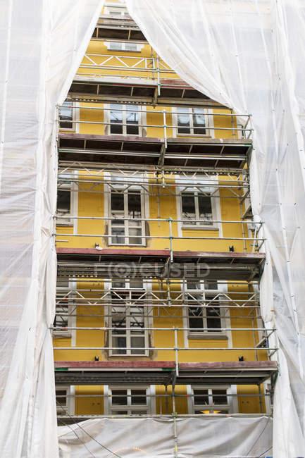 Восстановлено старое желтое здание под леса — стоковое фото