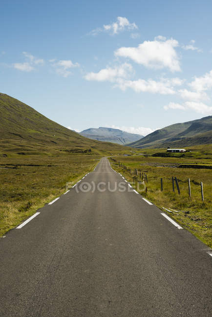 Asphalted country road leading towards mountains against sky — Stock Photo