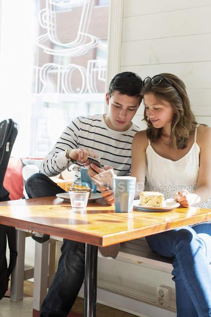 Casal usando telefones celulares enquanto está sentado na mesa do restaurante — Fotografia de Stock