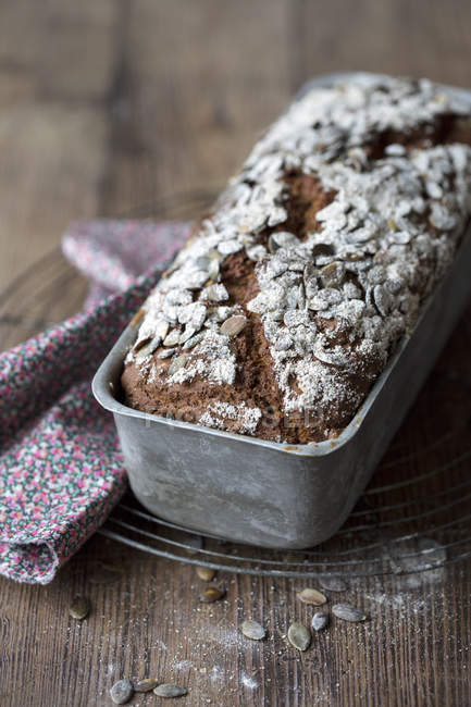 Primo piano del pane di grano intero nel contenitore sul tavolo disordinato — Foto stock