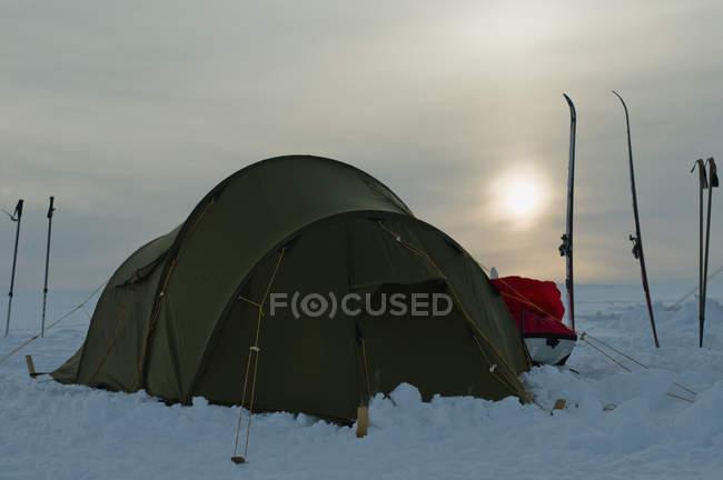 Tente dans la neige contre le coucher de soleil au ciel nuageux — Photo de stock