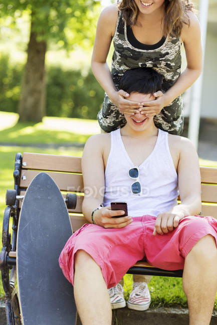 Happy girlfriend covering boyfriend's eyes in park — Stock Photo