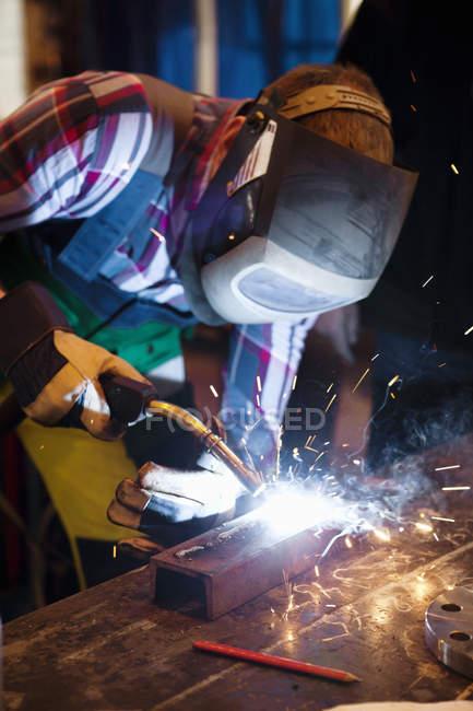 Vista de tres cuartos de la longitud del soldador durante el trabajo - foto de stock