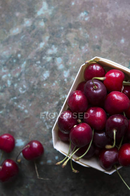 High angle view of cherries in container on stony surface — Stock Photo