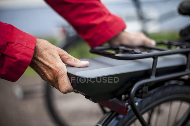 Abgeschnittenes Bild einer Seniorin, die Batterie auf dem Rücksitz eines Elektrofahrrads einsetzt — Stockfoto
