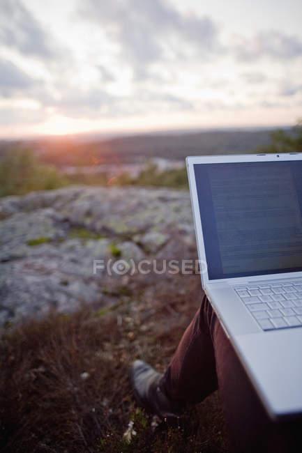 Человек с ноутбуком на коленях сидит на открытом воздухе — стоковое фото