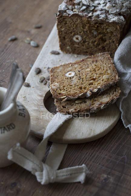 Vista di alto angolo di fette di pane integrale sul tagliere — Foto stock