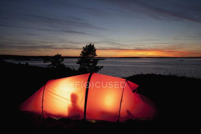 Lumière dans la tente contre le ciel nuageux de la soirée — Photo de stock