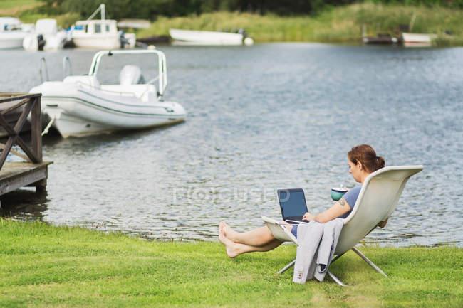 Visão lateral de comprimento total da mulher madura usando laptop na cadeira de praia no lago — Fotografia de Stock