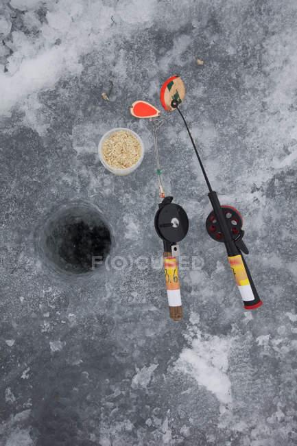 Vista de ángulo alto de cañas de pescar y peces cebo en lago congelado - foto de stock