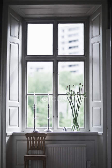Wooden Chair near window-sill with candlesticks and vase of flowers — Stock Photo