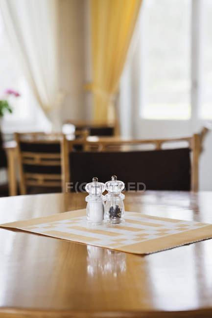 Скла шейкері солі і перцю на порожній дерев'яний обідній стіл — стокове фото