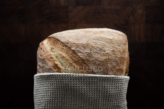 Крупным планом буханки хлеба, завернутые в салфетке на деревянный стол — стоковое фото