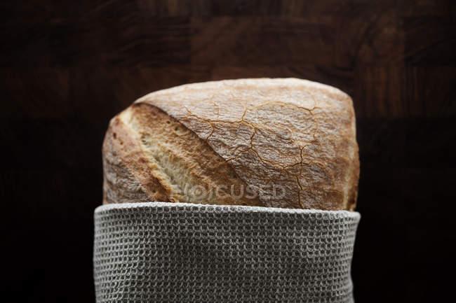 Primo piano della pagnotta di pane avvolto in un tovagliolo sulla tavola di legno — Foto stock