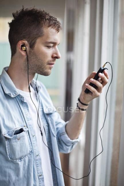 Seitenansicht eines jungen Mannes, der per Handy Musik hört — Stockfoto