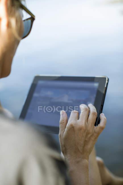 Imagem cortada de mulher adulta média usando tablet digital ao ar livre — Fotografia de Stock