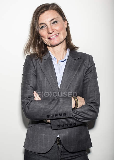 Portrait of confident mature businesswoman standing against wall — Stock Photo