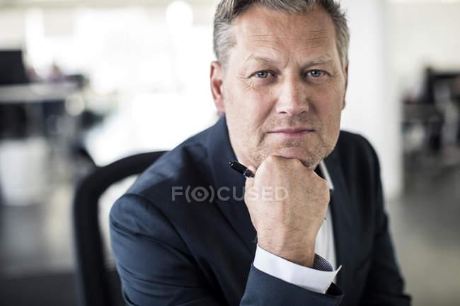 Retrato do homem de negócios maduro confiável que senta-se com mão no queixo no escritório — Fotografia de Stock