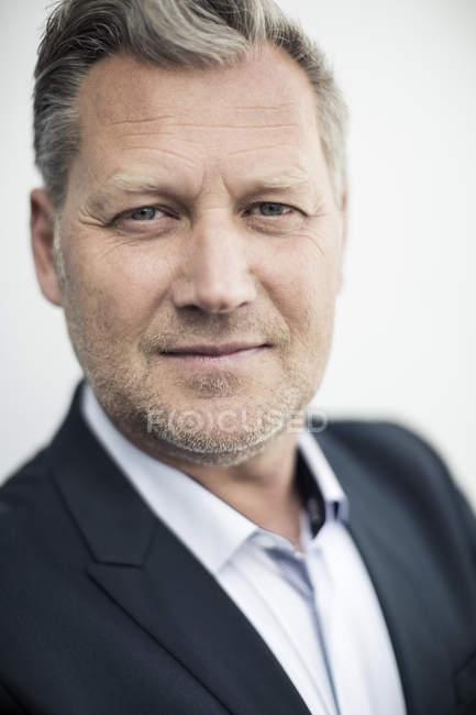 Close-up portrait of confident mature businessman against clear sky — Stock Photo