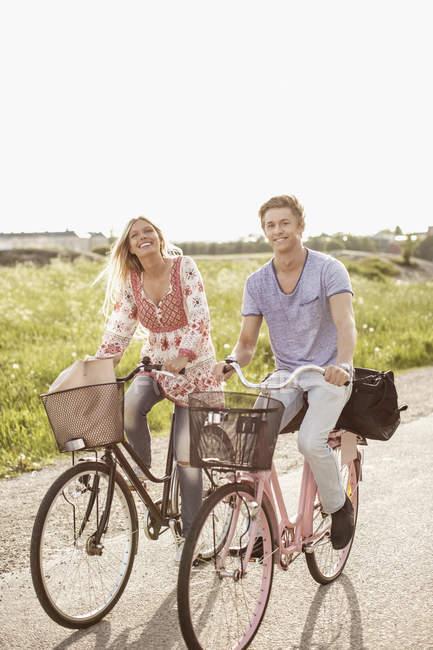 Retrato de jovem casal de ciclismo na estrada de campo — Fotografia de Stock