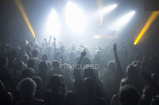 Rays of spotlights over crowded dance floor at disco — Stock Photo