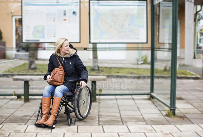 Disabled woman in wheelchair waiting at bus stop — Stock Photo