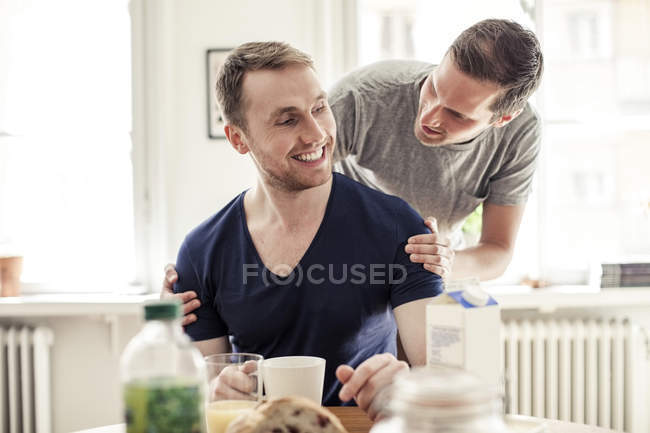 Young gay man looking at partner while having breakfast in house — Stock Photo