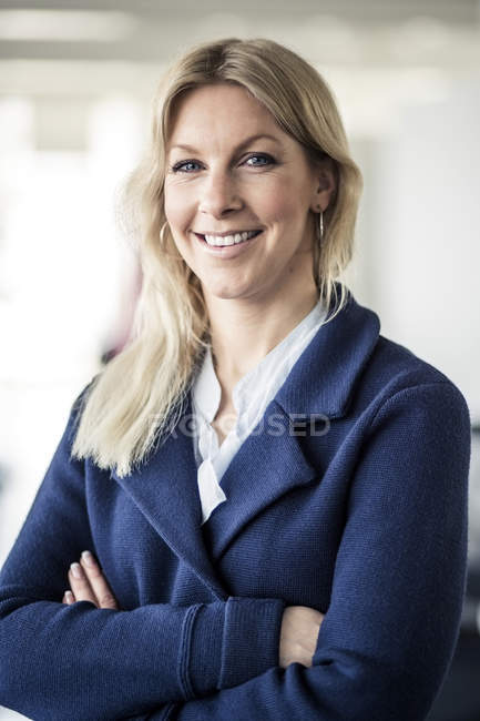 Portrait of happy mid adult businesswoman standing arms crossed in office — Stock Photo