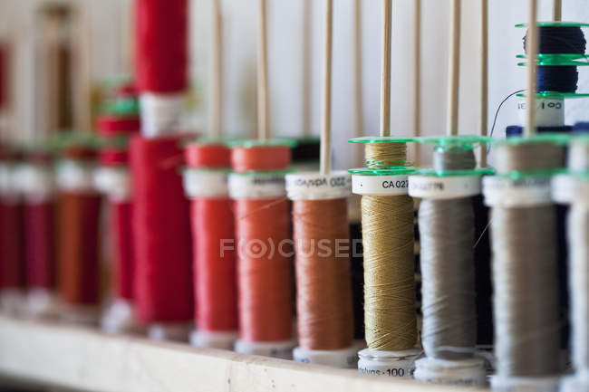 Group of sewing threads in row on shelf — Stock Photo