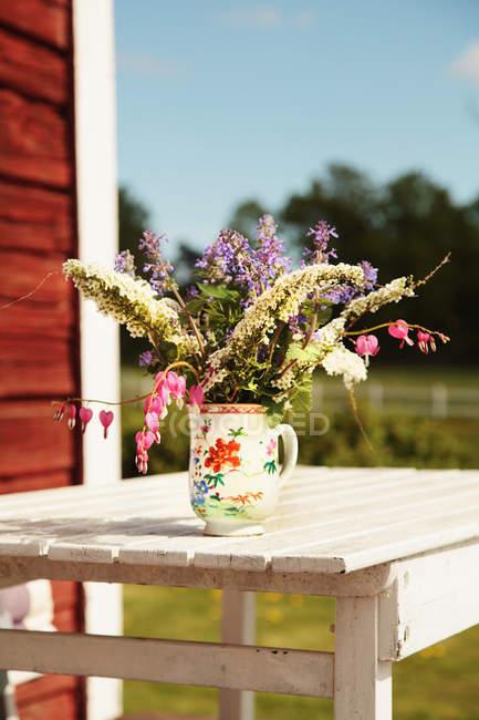 Ramo de flores de primavera en maceta sobre mesa de madera al aire libre - foto de stock