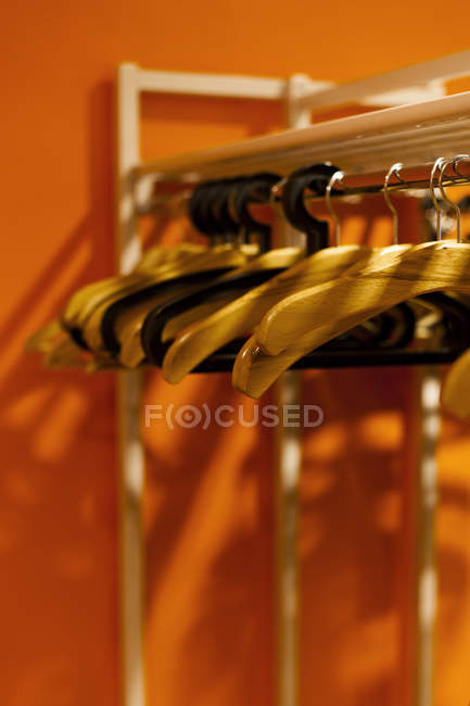 Coat hangers hanging on clothes rack in cabinet — Stock Photo