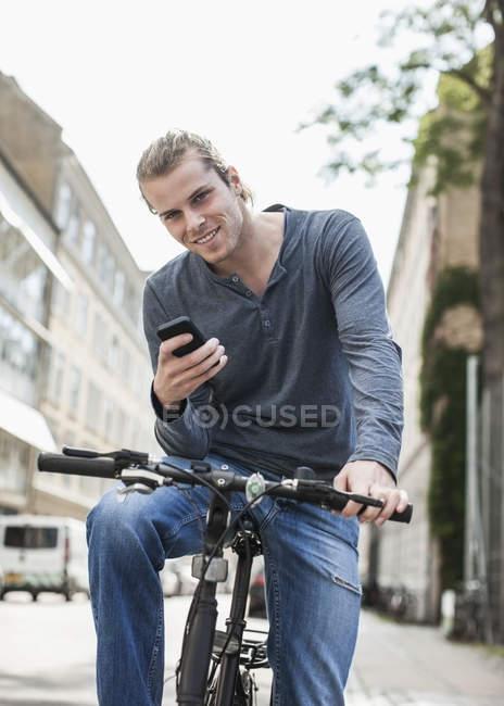 Retrato de jovem confiante com telefone celular sentado na bicicleta na rua — Fotografia de Stock