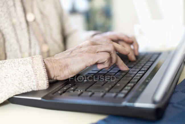 Midsection of senior woman using laptop at home — Stock Photo