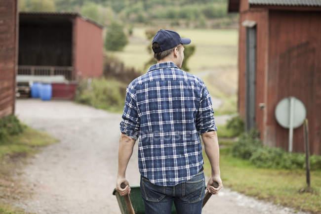 Передній вид фермера, який штовхає тачку на сільській дорозі. — стокове фото