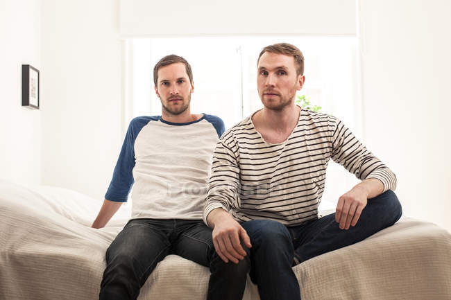 Portrait of homosexual couple sitting on bed at home — Stock Photo