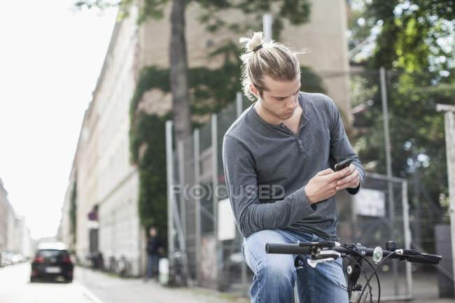 Молодой человек разговаривал по мобильному телефону, сидя на велосипеде на улице — стоковое фото