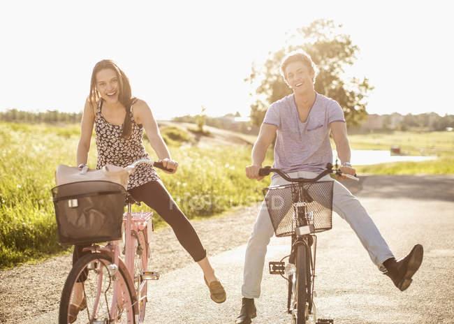 Портрет щасливої молодої пари з розставленими ногами на велосипеді по сільській дорозі. — стокове фото