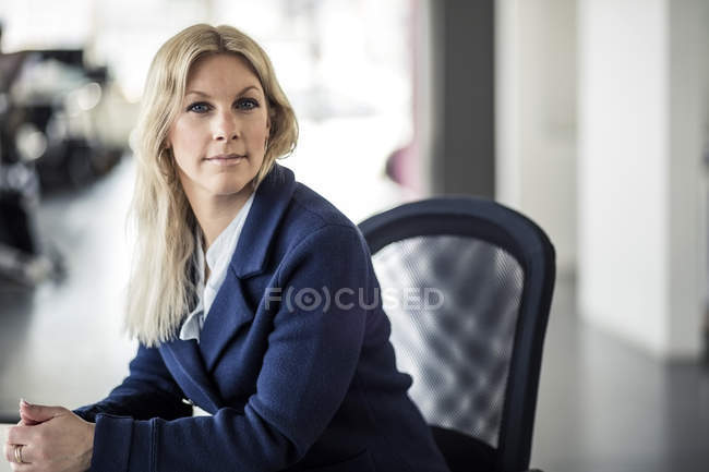 Portrait of confident mid adult businesswoman sitting on chair in office — Stock Photo