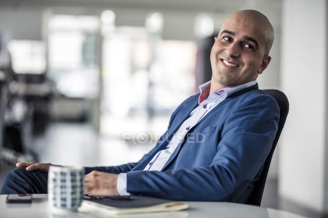 Mitte erwachsener Geschäftsmann schaut weg, während er am Schreibtisch im Büro sitzt — Stockfoto